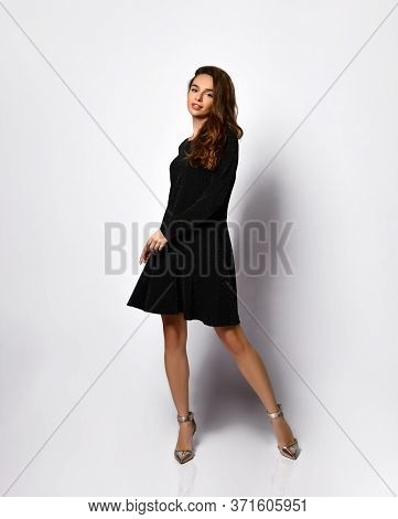 Model With Fluttering Dark Hair In A Velvet Black Dress And Silver Shoes Posing On A Light Backgroun