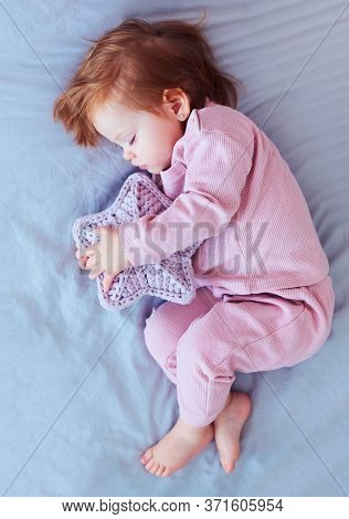 Beautiful Redhead Baby Girl Cuddles Up To The Knitted Star, Sleeping Peacefully On The Bed