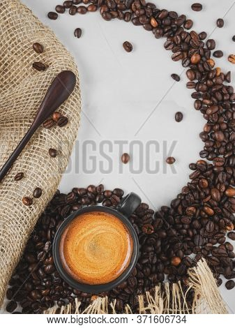 Fresh Roasted Coffee Beans And A Cup Of Hot Espresso With Froth, Located Below On A Wide White Backg