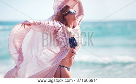 Beautiful Young Woman Enjoying Summer Breeze At The Beach During Vacation