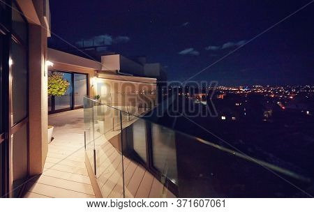 Rooftop Patio With Glass Balustrade And City View At Night