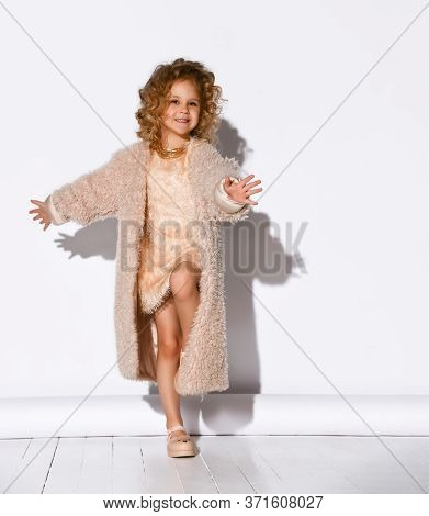 Charming Little Girl Dressed In A Punk Fluffy Coat And Sandals, Dancing Happily With A Charming Smil