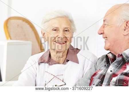 Happy senior couple sitting together happily in senior home