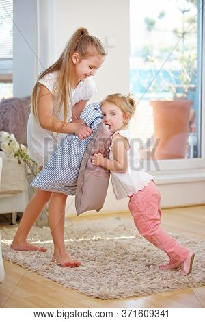 Two children play pillow fight at home with pillows