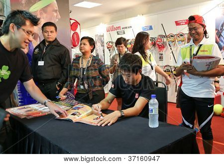 KUALA LUMPUR - SEP 22: Kei Nishikori of Japan autographs for fans in a brand promotion event of the ATP Tour Malaysian Open 2012 on September 22, 2012 at the Putra Stadium, Kuala Lumpur, Malaysia.
