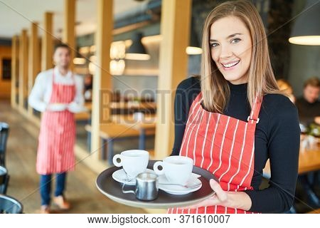 Young woman serving as a waitress in cafe or restaurant carries a tray of coffee cups
