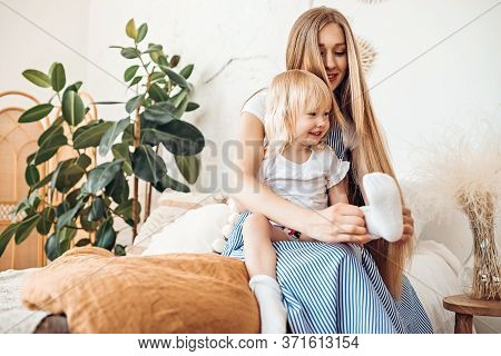 Young Mom Or Babysitter Puts On Socks To A Three Year Old Child