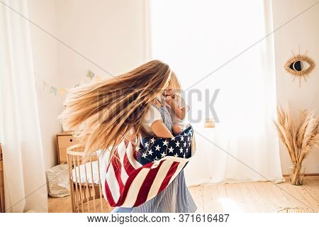 Young Mother Or Babysitter With A Little Girl In Her Arms Spin In The Middle Of The Room Celebrating