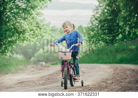 Girl Rides A Childrens Bike With Shallow Depth Of Field