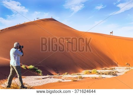 Grand trip to Africa, Namib Naukluft desert. Tourist photographs a picturesque orange dunes. The dry lake Sussussflay. The concept of exotic, extreme and photo tourism
