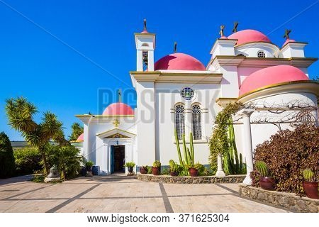 Capernaum on the shores of Lake Tiberias. Israel. Snow-white church building with pink domes and golden crosses. Place of worship and pilgrimage. The concept of religious pilgrimage and photo tourism