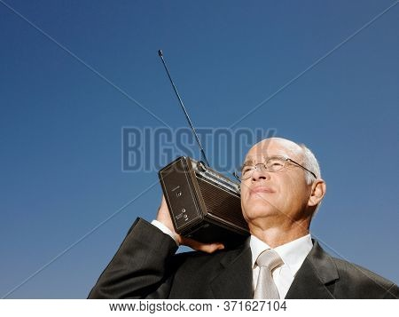 Businessman with radio on shoulder head and shoulders