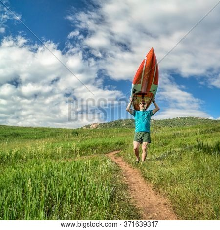 senior male paddler is carrying a long racing stand up paddleboard (SUP) downhill on a trail in early summer - Lory State Park, Colorado