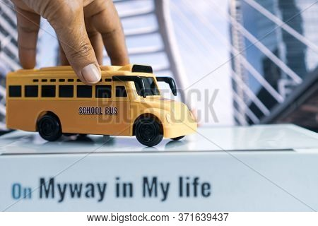 Hands Holding School Bus For Student Transport Children Transports Service On Stack Books With Word