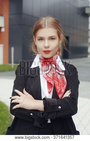 Girl Stewardess, Blonde With A Tail And Red Lips, In A Red Neckerchief Looks At The Camera. Girl Wit