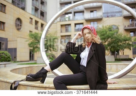 A Girl In A Business Suit With A Red Scarf On Her Head Against The Background Of A Building, Sits On