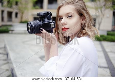 Photographer Girl Walks Around The City With A Reflex Camera. A Young Blonde Learns To Take Pictures