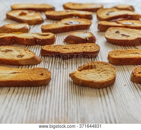 Wheat Rusks On A Wooden Background. Background From Rusks. Photographed Close-up.