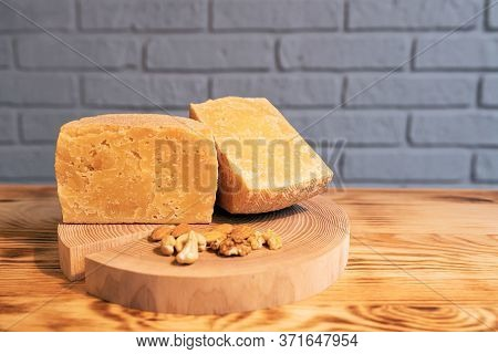 A Head Of Aged Cheese Cut In Half On A Wooden Board With Various Nuts On The Background Of A Brick W