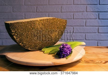 A Large Piece Of Aged Cheese With Spices, Next To A Purple Flower.