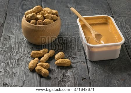 Wooden Bowl With Peanuts And A Plastic Container With Peanut Paste. Natural Peanut Cream.