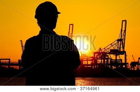 Silhouette of a docker, overlooking the cranes at the docks at sunset