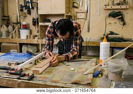 Working Process In The Carpentry Workshop.a Man In Overalls Works In A Carpentry Workshop.profession