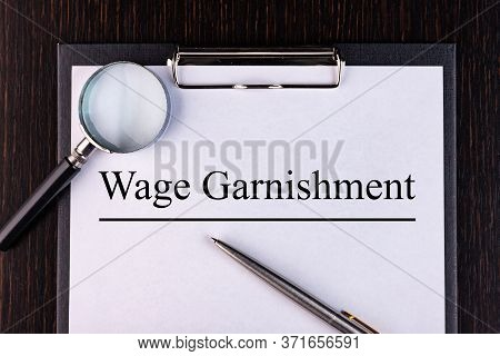 Text Wage Carnishment Is Written On A Notebook With A Pen And A Magnifying Glass Lying On The Table.