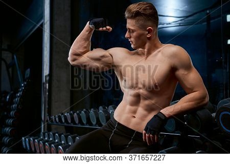 Front View Of Shirtless Bodybuilder Posing And Looking At Tensed Arm, Leaning On Stand With Dumbbell