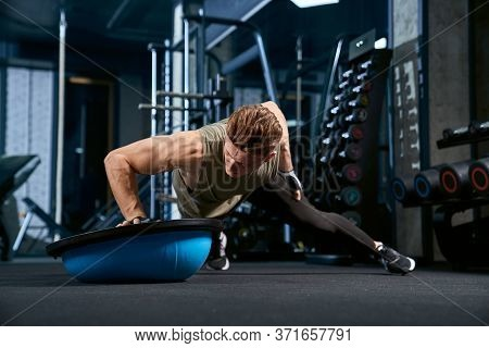 Front View Of Muscular Caucasian Man Training On Floor Using Balance Half Ball. Close Up Of Young Sp