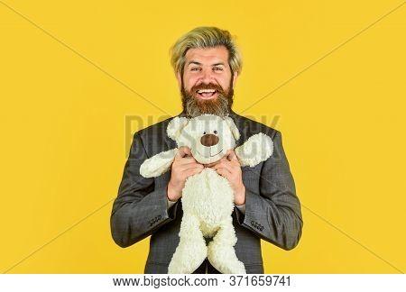 Still Childish In Soul. Happy Businessman Hug Teddy Bear Yellow Background. Bearded Man With Toy Fri