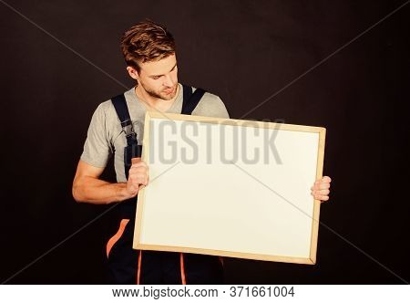 Handsome Repairman. Man Repairman Builder Work Clothes. Plan Repair Work Using Blueprints Or Diagram