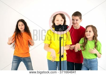 Group Of 10 Years Old Children Smiling And Shoots A Video. Selfies. The Phone Is Mounted On A Tripod