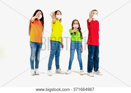 Group Of Schoolchildren Children In Colorful T-shirts And Medical Masks Showing Crossed Hands Gestur