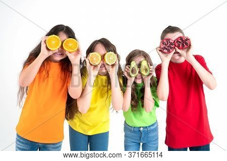 Three Girls And A Boy Using Fruits As Glasses On A On A White Background. Group Of Happy Children Wi