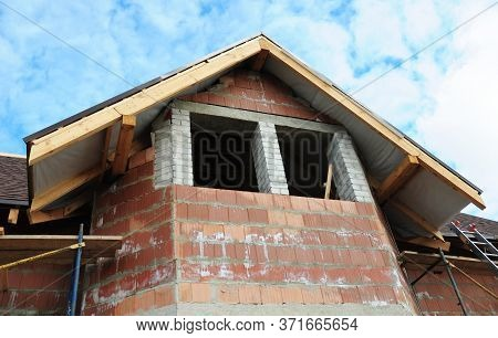A Close-up On Attic, Mansard And Roofing Construction With Unfinished Soffit, Eaves, Fascia And Wind