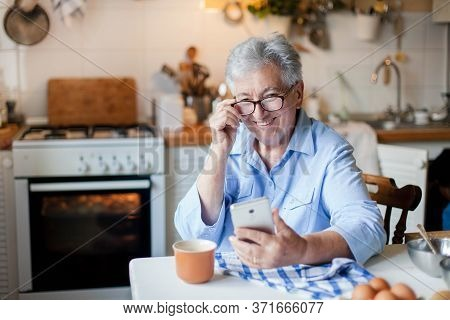 Senior Woman Using Mobile Phone At Home Kitchen. Happy Retired Person Shopping Online. People Connec