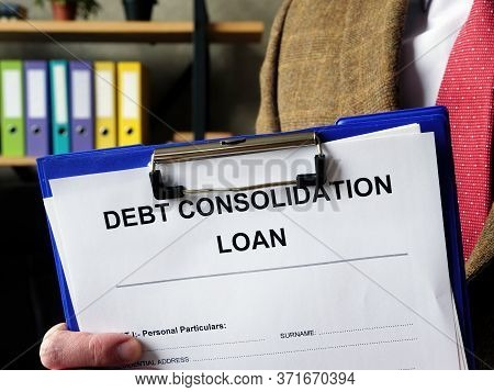 Banker Offers Debt Consolidation Loan Documents For Filling In.