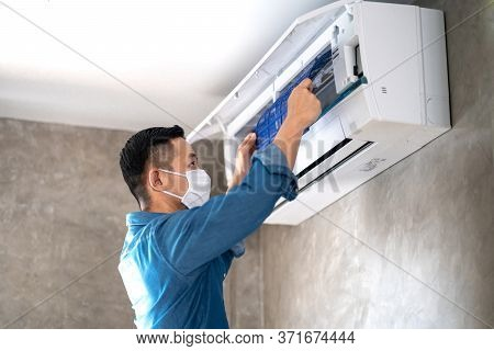 Technician Man Repairing ,cleaning And Maintenance Air Conditioner On The Wall In Bedroom Or Office