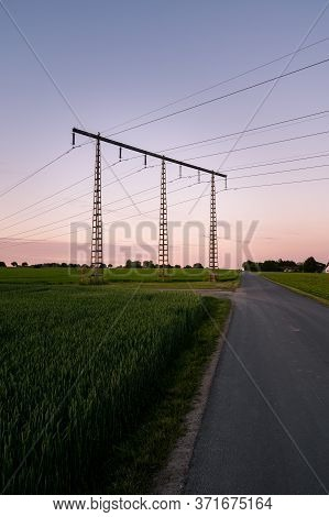 Electricity Pylons Close To A Rural Road With Green Crops Growing During Summer Sunset In Skåne (sca