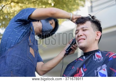 Asian Businessman Making Haircut At Home Garden. Social Distancing And New Normal Lifestyle.