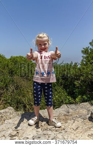 Israel. Haifa. 06.06.2020.a Joyful Little Girl Stands On Top Of A Mountain With Arms Outstretched Fo