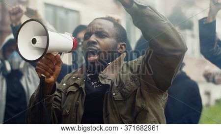 African-american Young Handsome Man Screaming In Megaphone At Protest For Human Rights Outdoors In S