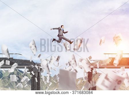 Businessman Jumping Over Gap In Bridge Among Flying Papers As Symbol Of Overcoming Challenges. Skysc