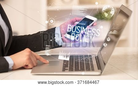 Side view of a business person working on laptop with BUSINESS POLICY inscription, modern business concept