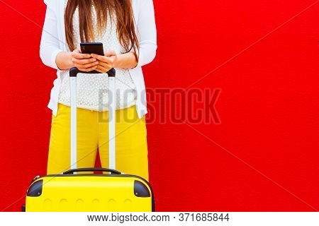 Woman With A Yellow Suitcase Reading Messages On Her Mobile Phone Leaning Against A Red Wall