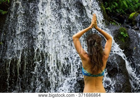Close Up Of Yoga Woman Raising Arms With Namaste Mudra In Front Of Waterfall. View From Back. Yoga R