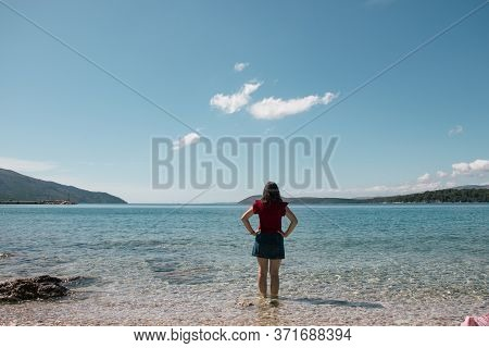 Woman Seen From Behind Entering The Sea Clothed. Standing In Clear Beautiful Sea On The Island Of Hv