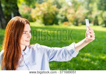 Young Redhead Woman Taking Selfie Photo On Green Field. Close Up Portrait Of Charming Girl With Smar
