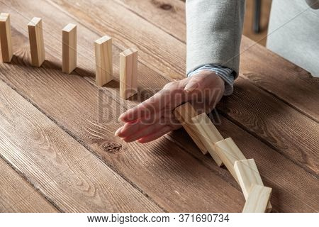 Businesswoman Protecting Dominoes From Falling On Wooden Desk. Business Assistance And Leadership In